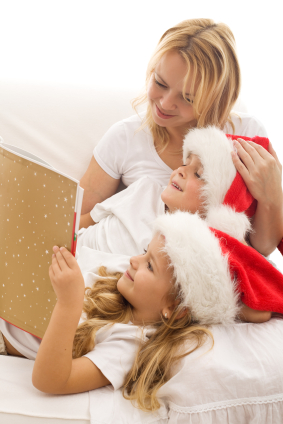 mother reading to children in santa hats